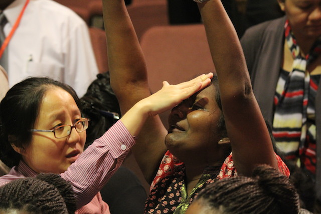 A sister-in-Christ lifting her hands for God to heal her