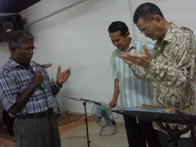 Pastor Moses (left) praying for a brother-in-Christ