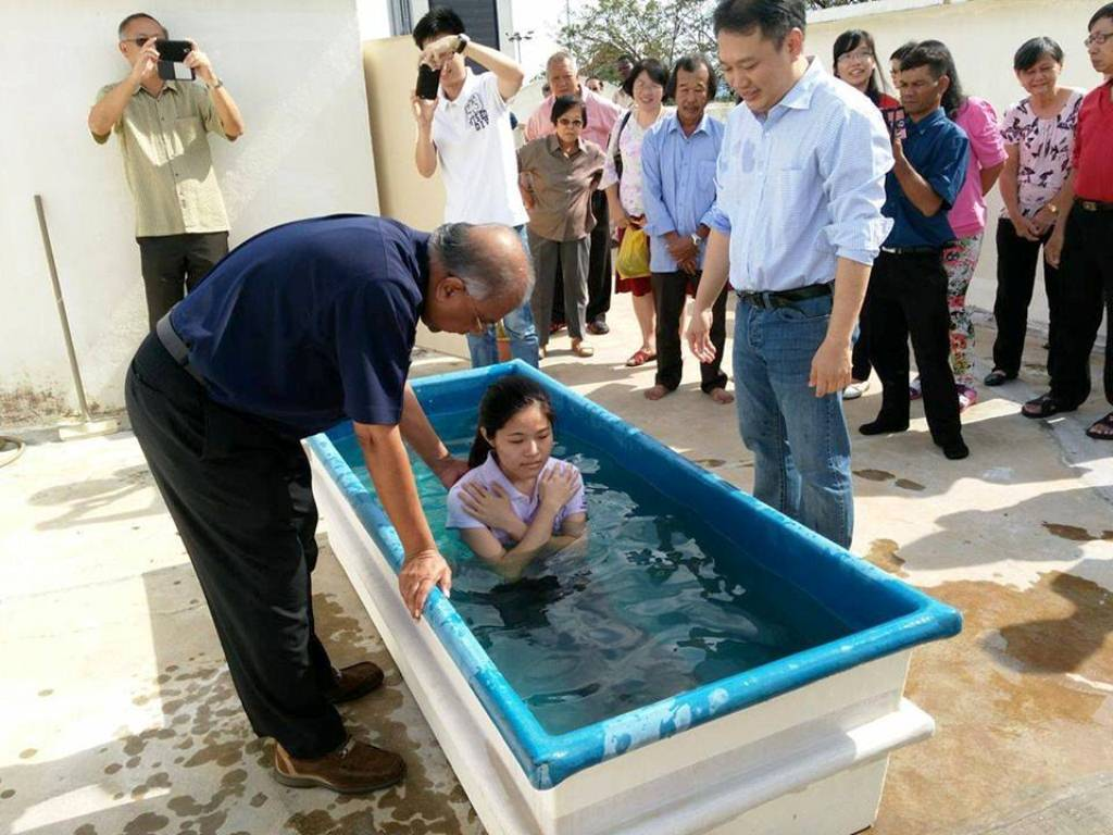 The baptism of one of the members by Elder Jacob Yeng (right) in church