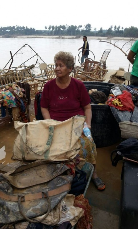 A flood victim sitting in a pile of ruins from the flood