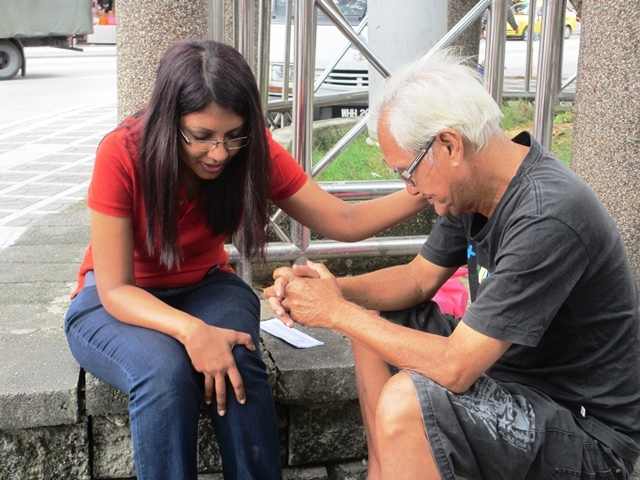 Veron praying for an elderly street person