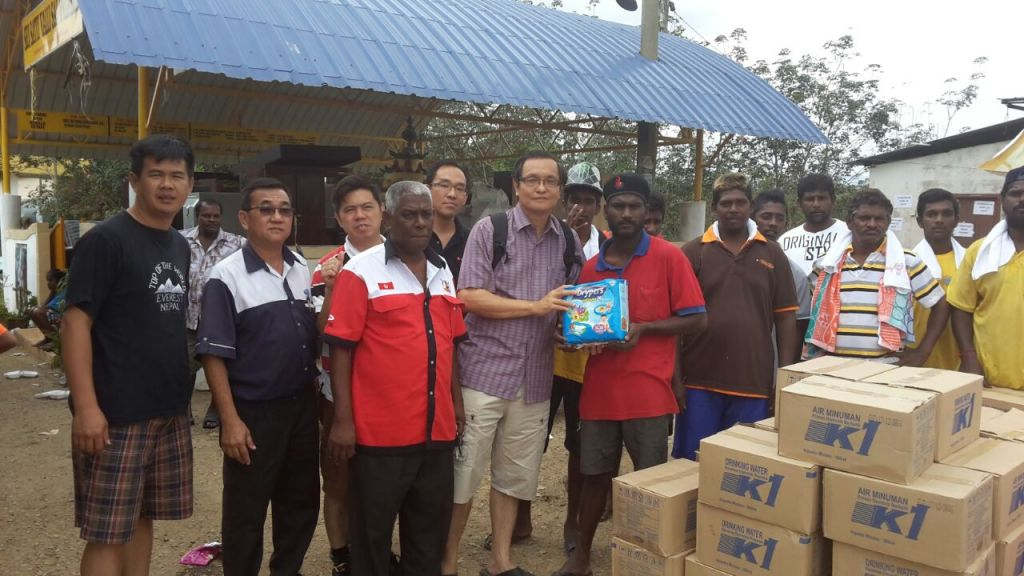Pastor Henderson Wee (in purple shirt) passing supplies to flood victims