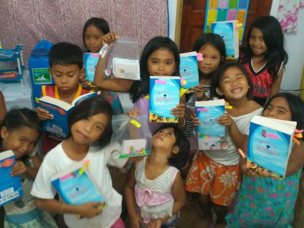 The kids ecstatic to receive brand new Bibles (in her tiny studio)