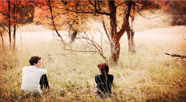 girl-and-boy-sitting-outside-away-from-each-other