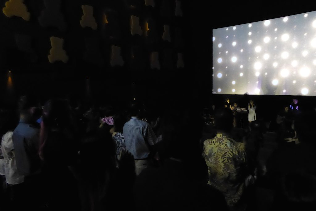 Everyone standing in the cinema theater worshiping God