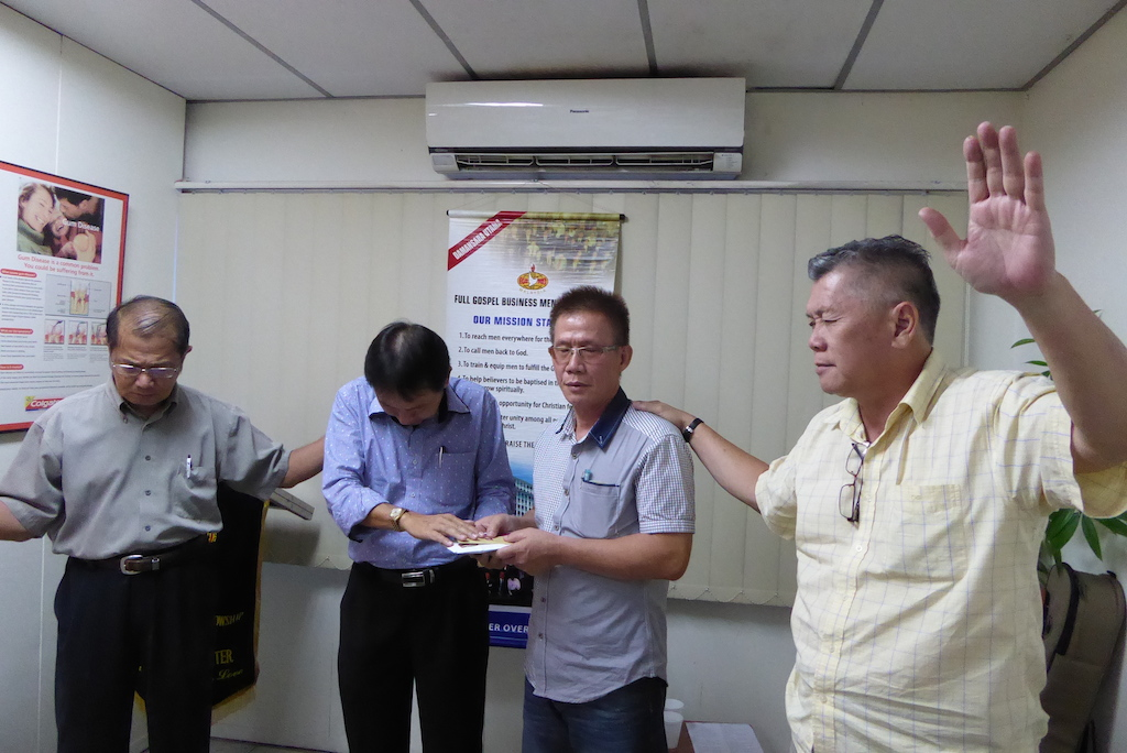 Daniel Liew (right) who was part of Malaysian Care and had reached out to Sam in prison, praying for Sam (2nd from right) after the sharing