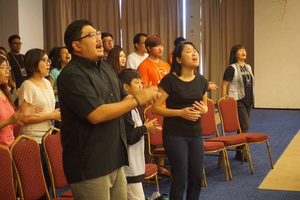 Pastor Damien Chua and his wife Mei Ying worshipping God