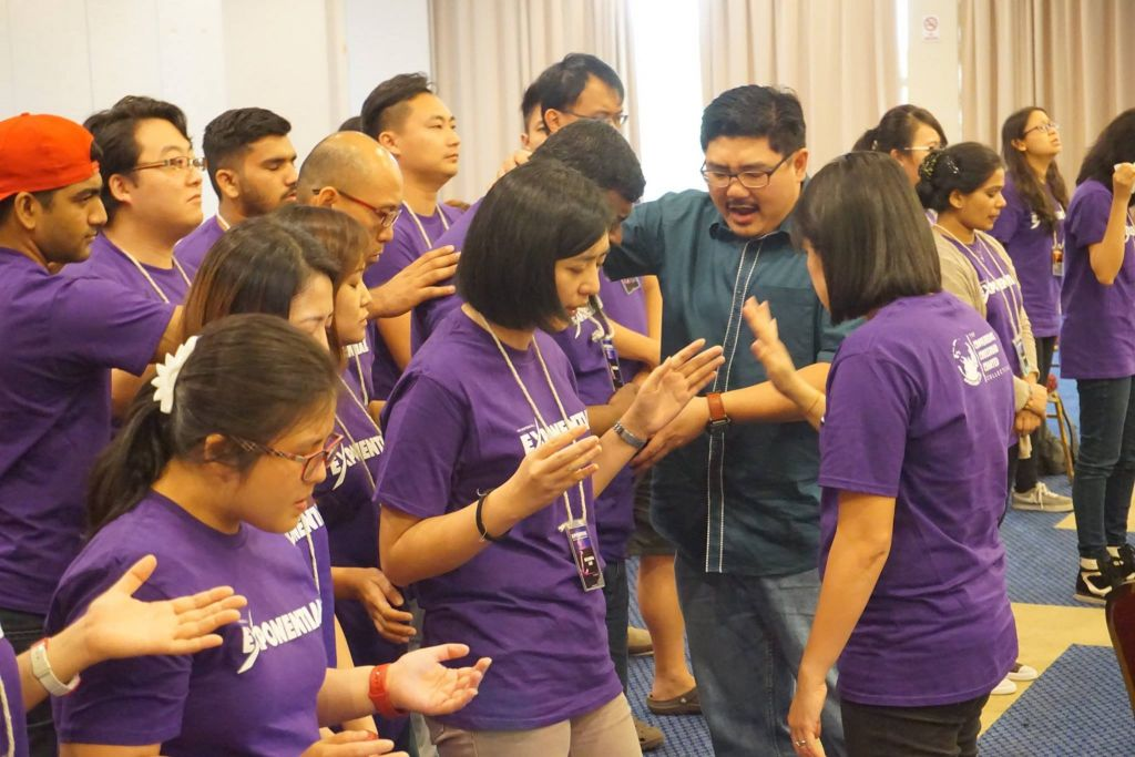 Pastor Damien Chua praying for the participants of Exponential camp in Taiping Golf Resort