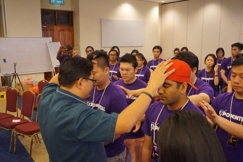 Pastor Damien Chua praying for the young adults of Exponential Camp at Taiping Golf Resort