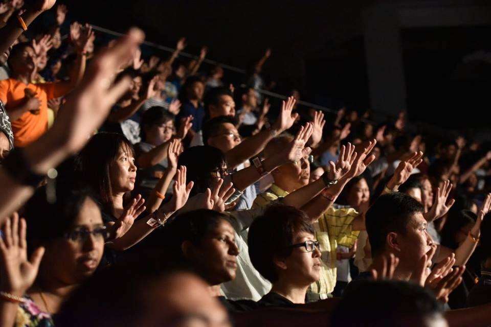 Attendees lifting their hands worshipping God