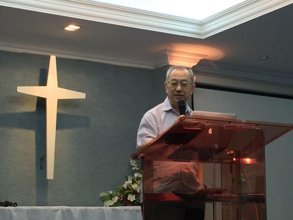Pastor Derek Hong preaching onstage