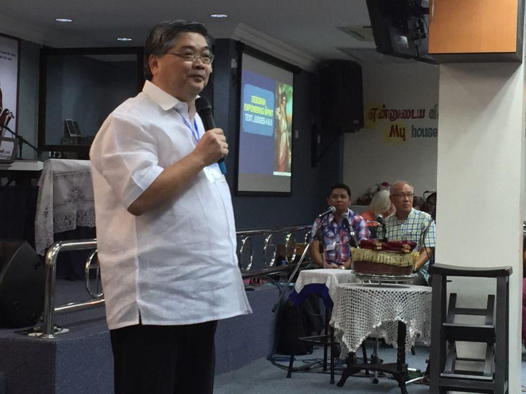 Pastor Alan Tan preaching onstage in PAAG