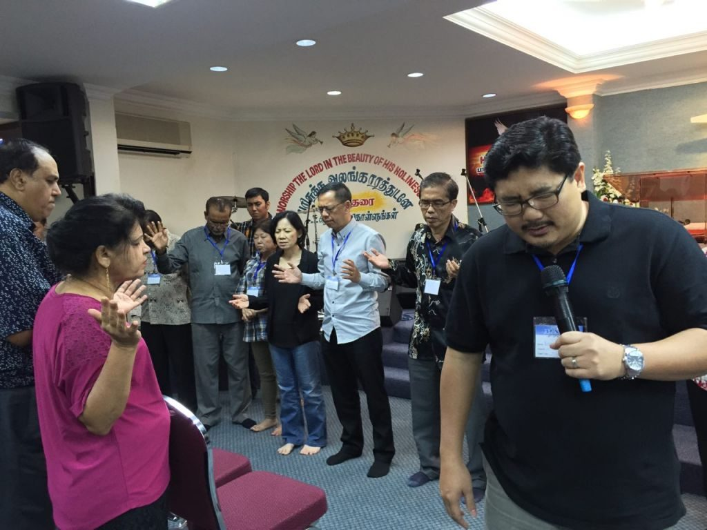 Pastor Damien Chua praying for the church pastors and leaders of PAAG