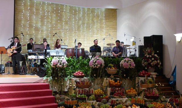 The musicians of Tabernacle of David onstage, accompanied with an array of fruits