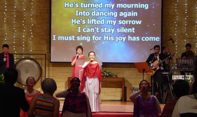 Pastor Irene Chong worshipping God onstage
